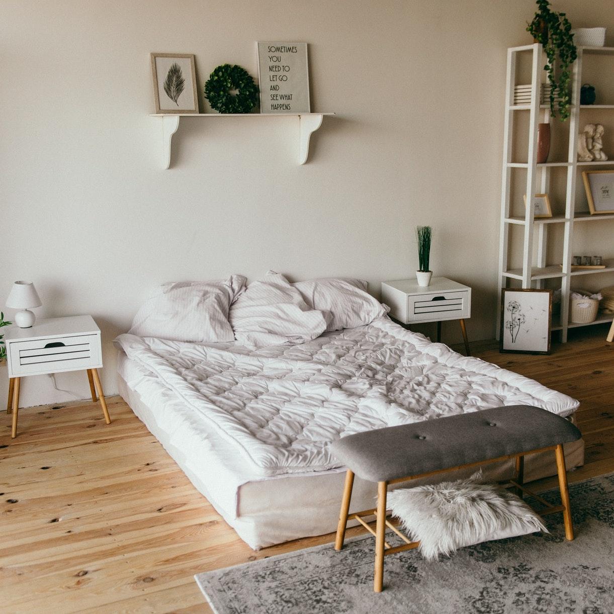 Bett mit weißem Bezug auf hellem Parkett